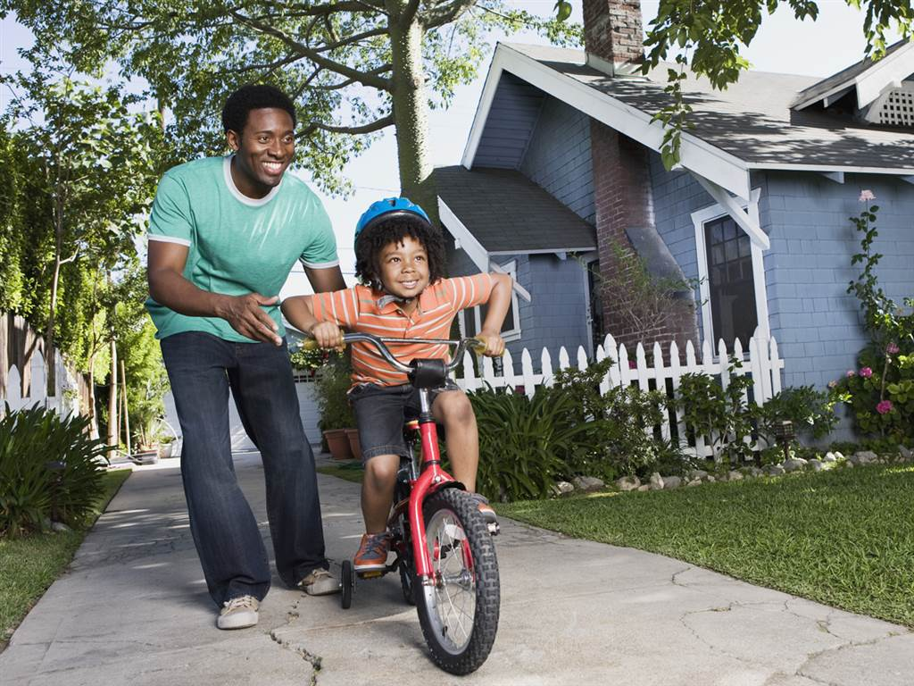 child biking with his father