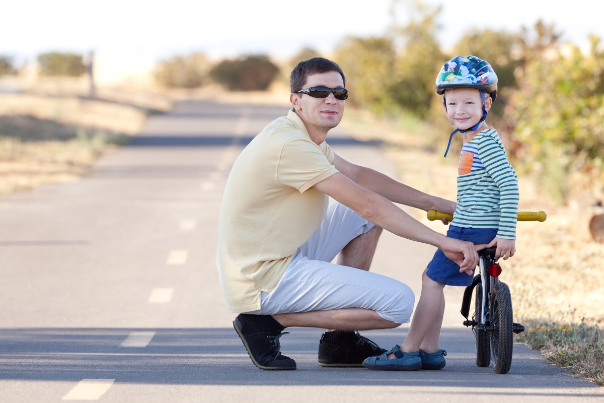 a dad and a son learning to ride a bike