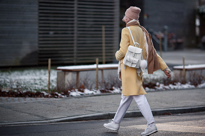 Yellow coat - white backpack and sneakers.  An image for autumn or winter