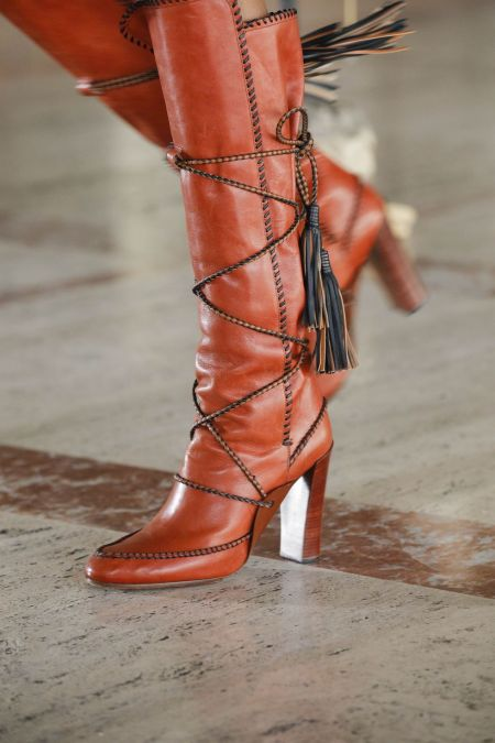 Red boots with decorative lacing and tassels