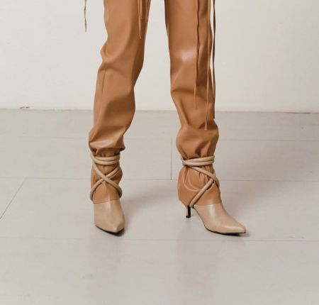 Beige boots with a pointed toe and decorative lacing